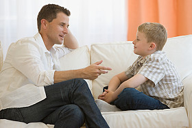 Father talking to son on sofa